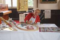 A lady demonstrating gilding in St Edwards Hall