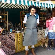 A craft stall with merchant dressed for the period